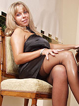 Donna in sexy black dress and black full fashion nylon stockings by the piano showing off her beautiful legs and feet